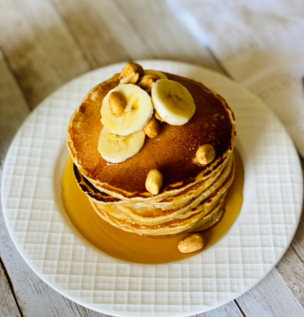 Peanut butter pancakes served in a plate with maple syrup, sliced bananas and roasted peanuts on top