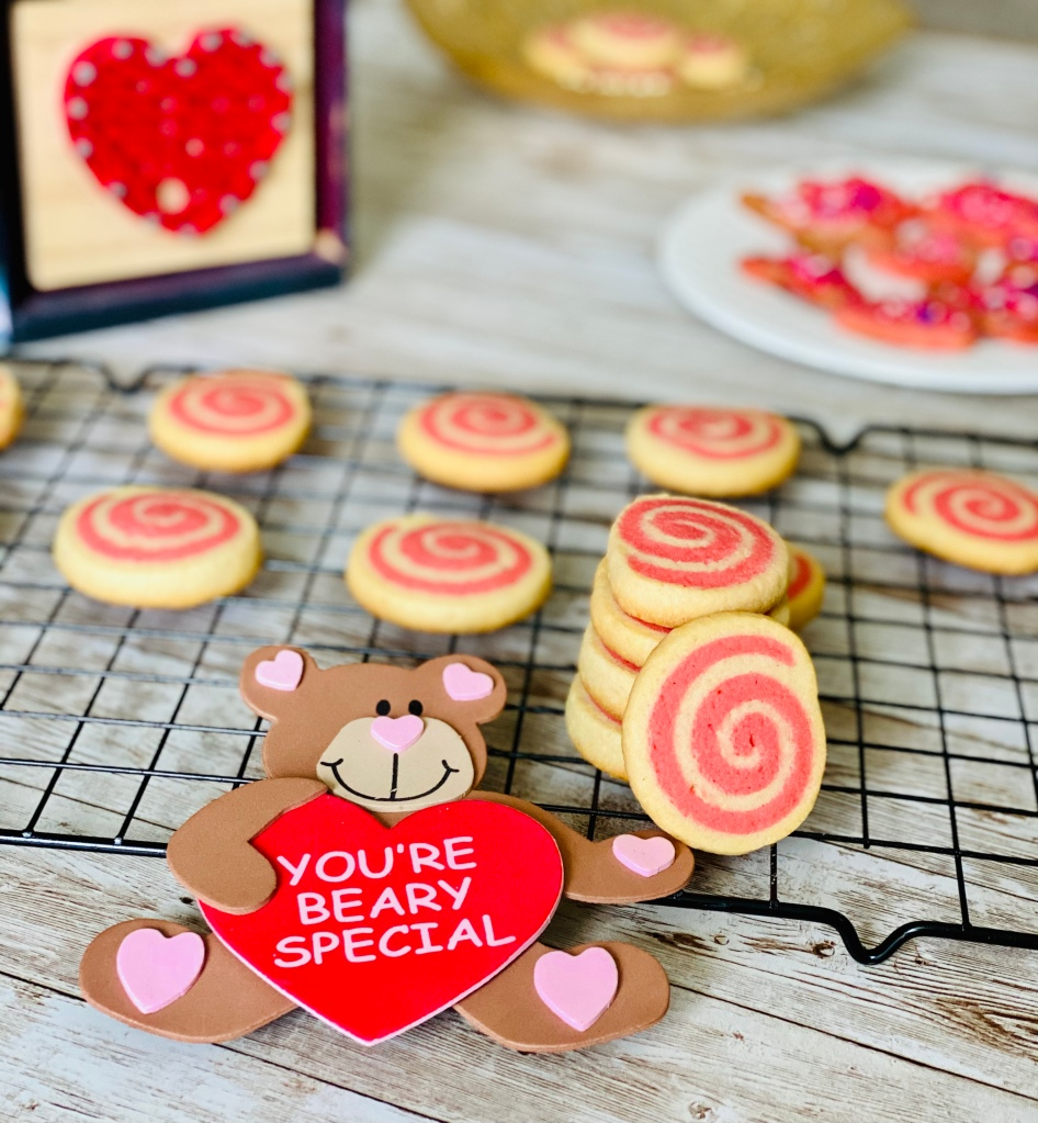Pin wheel cookies lying on a wire rack with Valentine's Day props around