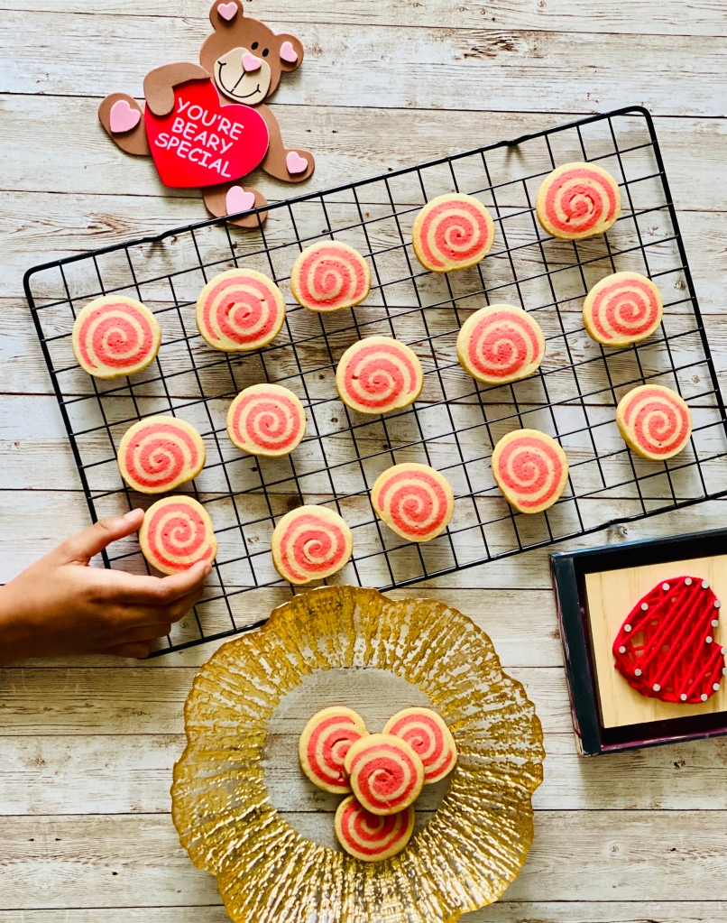 Pinwheel cookies on a wire rack with a little hand trying to grab a cookie and Valentine's Day props lying around